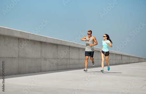 Leinwand Poster fitness, sport and lifestyle concept - happy couple in sports clothes and sungla
