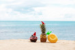 funny attractive pineapples and coconut in stylish sunglasses on the sand against turquoise sea. Wearing christmas hats. Christmas and new year vacation concept on tropical beach.