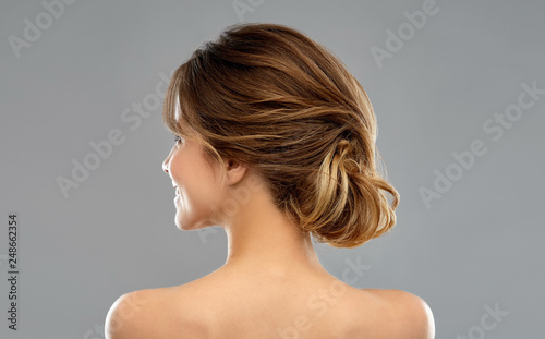 beauty and people concept - young woman with bare shoulders from back over grey background