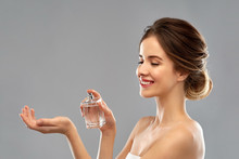 Perfumery, Beauty And Luxury Concept - Happy Smiling Young Woman Spraying Perfume To Her Wrist Over Gray Background
