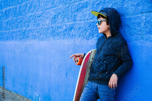 Valokuvatapetti Little skater plays with the board on a blue wall