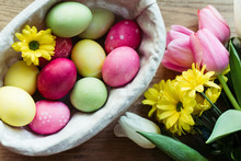 Closeup Bunch Of Fresh Flowers And Basket With Colored Eggs Placed On Lumber Tabletop