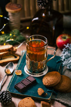 Piece Of Tasty Chocolate And Yummy Oatmeal Cookies Lying On Old Book Near Mug Of Aromatic Hot Tea