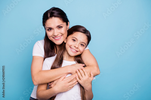 Fototapeta Close up photo amazing pretty two people brown haired mum mom small little daughter stand hugging piggy back lovely free time rejoice wearing white t-shirts isolated on bright blue background obraz