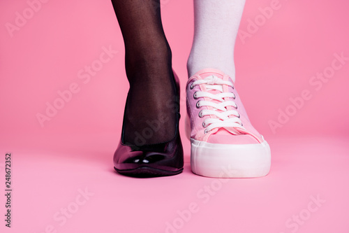 Obraz Cropped close-up view image concept photo of two different fit thin slim legs cozy comfort luxury luxurious elegant chic sporty comparison footgear isolated on pink pastel background - fototapety do salonu