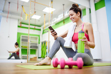 Full Length Side View Portrait Of Pretty Young Woman  Using Smartphone After Work Out And Smiling, Copy Space