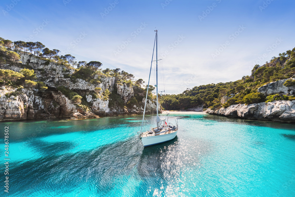 Fototapety, obrazy: Beautiful beach with sailing boat yacht, Cala Macarelleta, Menorca island, Spain. Yachting, travel and active lifestyle concept