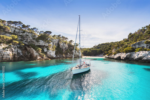 Foto op Plexiglas Mediterraans Europa Beautiful beach with sailing boat yacht, Cala Macarelleta, Menorca island, Spain. Yachting, travel and active lifestyle concept
