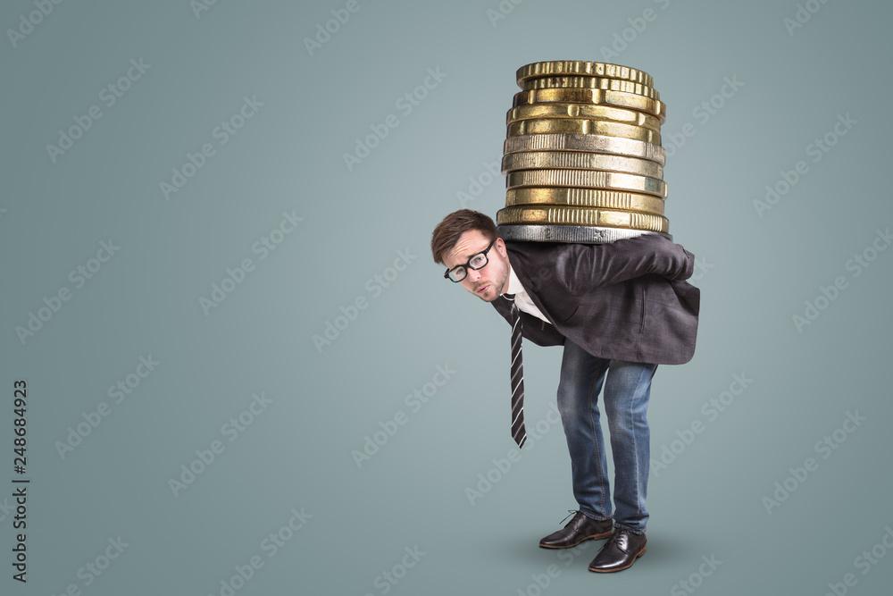 Fototapeta Geschäftsmann trägt einen riesigen Stapel Münzen auf dem Rücken