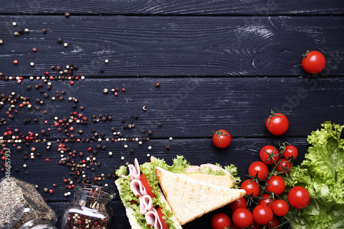 Photo  Tasty sandwiches with vegetables and pepper spices on black wooden table