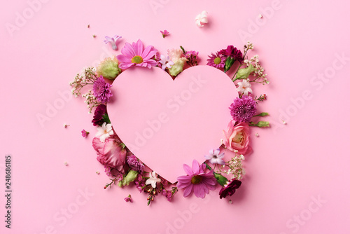 Creative layout with pink flowers, paper heart over punchy pastel background. Top view, flat lay. Spring, summer or garden concept. Present for Woman day