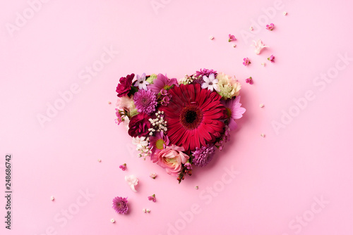 Fotomural  Heart shape made of spring flowers on pink punchy pastel background