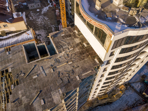 Fotografía  Aerial winter top view of modern developing city with tall apartment complex building under construction, parked cars, roofs and streets