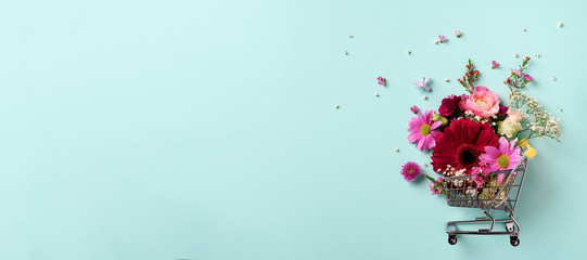 Kolica za kupovinu s cvijećem na plavoj prozirnoj pastelnoj pozadini. Natpis s prostorom za kopiranje. Pogled odozgo, ravno položen. Kreativni izgled. Svečana kupovina i prodaja. Pokloni za nju.