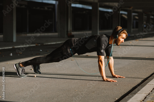 Fotografía  Young man doing push ups in the urban environment
