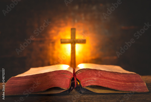 Obraz na płótnie Close up Bible and cross with light of candle background on wooden table