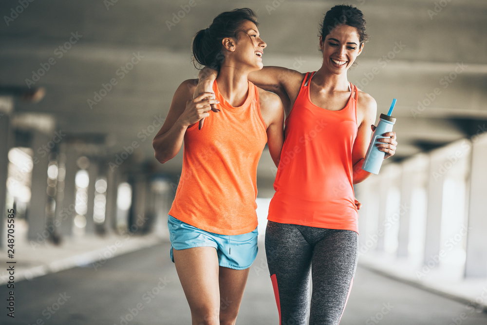 Fototapety, obrazy: Two female friends jogging on the city street under the city road overpass.They relaxing after jogging and making fun.Embracing each other.