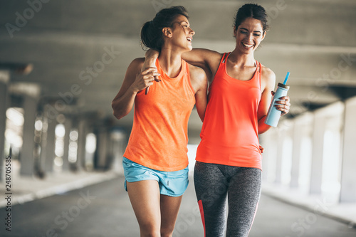Fotografia  Two female friends jogging on the city street under the city road overpass