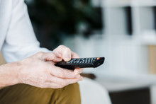Cropped View Of Senior Man Holding Remote Control In Hands