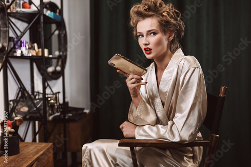 Photo Young beautiful woman with wavy hairstyle and red lips in silk robe sitting on c