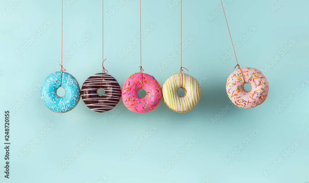 Fototapety, obrazy: Newton's cradle from doughnuts. Collision balls made from donuts. Harm of sugar, donuts time or healthy diet concept. Dependence on flavoring, diabetes problems, weight loss.