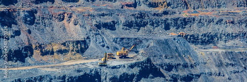 Fotografía  loading of mined iron ore in a pit to excavators in a cargo diesel dump truck