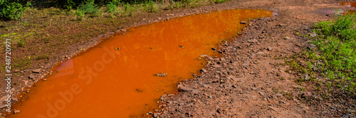 Photo puddle of water painted red with iron salts on a dirt road.