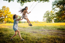 Mom Swinging Daughter On A Swi...