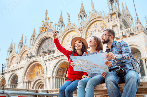 Foto  Group of happy friends travelers with map on San Marco Square in Venice