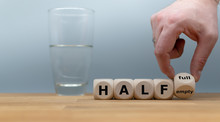 """Hand Turns A Dice And Changes The Expression """"half Empty"""" To """"half Full"""". A Half Full Glass Of Water Is Standing In Front Of A Grey Background."""