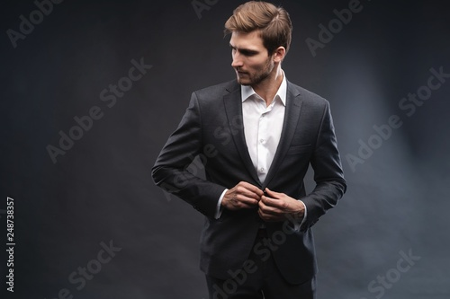 Fotografia Portrait of a handsome young businessman dressed in suit isolated over gray background