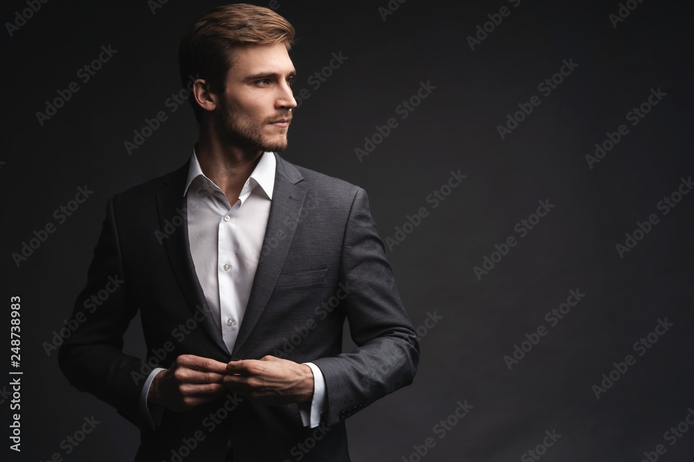 Fototapeta Portrait of serious handsome man in gray suit buttoning jacket