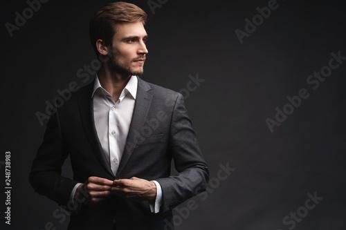 Fotografia, Obraz Portrait of serious handsome man in gray suit buttoning jacket