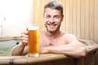 Męskie spa. Przystojny mężczyzna zażywa kąpieli w bali z woda termalną pijąc piwo kuflowe.