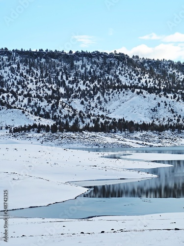 Photo  Hills covered in fresh snow and bright skies reflecting on the waters at Juniper Point at Prineville Reservoir in Central Oregon on a winter day