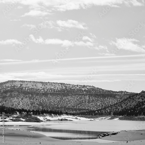 Fotografering  Hills covered in fresh snow and bright skies reflecting on the waters at Juniper Point at Prineville Reservoir in Central Oregon on a winter day