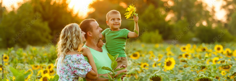 Fototapeta Happy family having fun in the field of sunflowers. Father hugs his son. Mother holding sunflower. outdoor shot