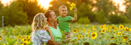 Obraz Happy family having fun in the field of sunflowers. Father hugs his son. Mother holding sunflower. outdoor shot - fototapety do salonu