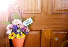 Happy May Day Traditional Gift Of Spring Flowers In Orange Cone Hanging From Door Handle On Wooden Door, With Lens Flare.