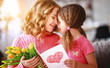 happy mother's day! child daughter gives mother a bouquet of flowers and postcard.