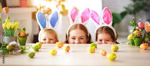 Fotografering Happy easter! family mother and children with ears hare getting ready for holiday