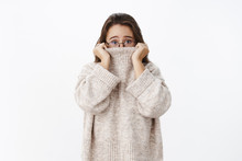 Indoor Shot Of Insecure Worried Young Cute Woman In Glasses With Brown Hair Pulling Collar Of Sweater On Nose And Frowning Nervously As Looking Scared At Camera, Posing Anxious Over Gray Background