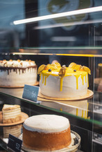 The Girl Waiter Fills The Confectionery Showcase, Placing Her Cakes And Pastries, A View Through The Glass Of The Refrigerator For Desserts.cake And People In Cafe Concept.