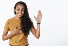I Swear Geez. Portrait Of Cute And Friendly Happy Young Nice African-american Girl With Curly Hair Raising Palm And Holding Hand On Heart As Making Oath Smiling Joyfully Over Gray Background
