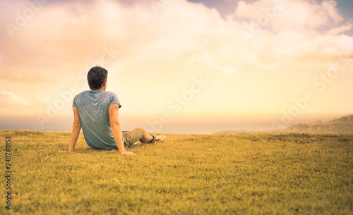 Photo Young man sitting in a field watching the sunset