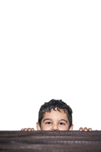 A Kid Peeking Out From Under The Table. Cute Young Mixed Race 4-5 Years Old Boy Looking Over Wooden Desk On White Background With Copy Space
