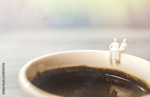 Fotografia  Miniature couple in love sitting on Coffee cup edge, Valentines day concept