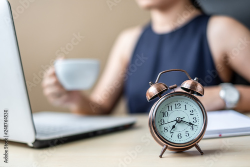 Fototapeta Close up alarm clock with young Businesswoman using laptop analysis marketing plan and drinking coffee in the morning. Business, Finance and lifestyle concepts obraz na płótnie