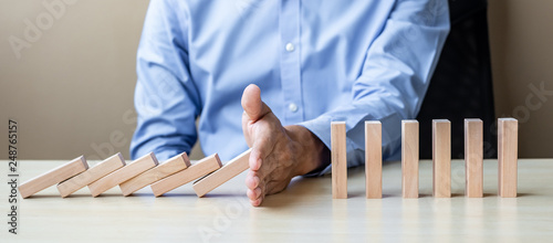 Canvas Print Businessman hand Stopping Falling wooden Blocks or Dominoes
