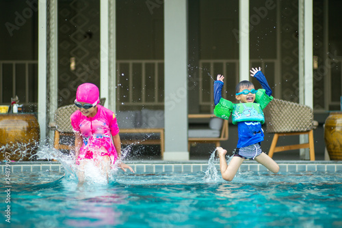 Fotografia  Happy sister and brother enjoy jumping into the swimming pool